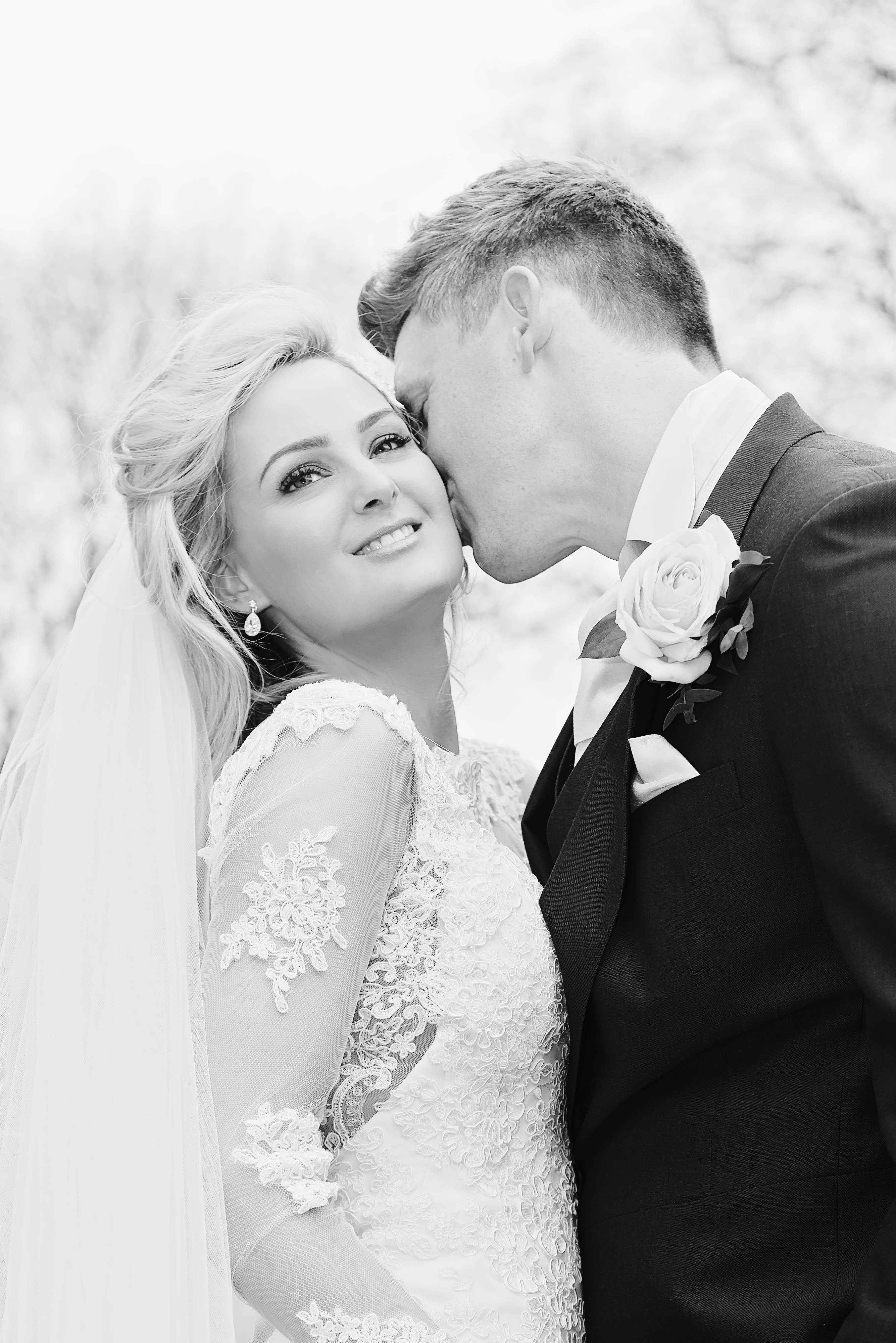 Beautiful portrait of groom kissing bride's cheek in black and white at Shooters Hill Hall