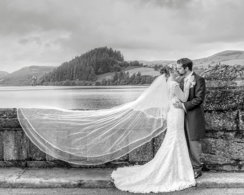 Award winning wedding pohotgraph of bride and groom posing on the Lake Vyrnwy Dam while the bride's veil blows in the wind by Amrose Photography