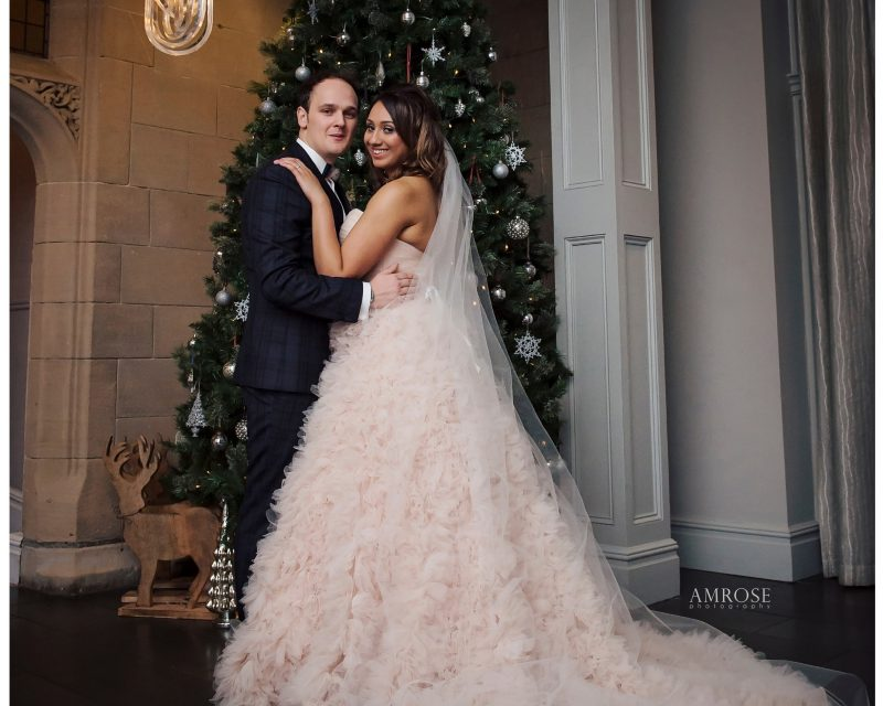 Bride and groom pose in front of Christmas tree