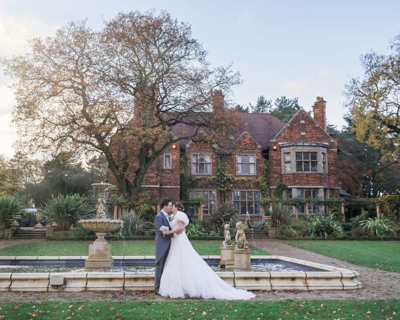 Landscape photo of the bride and groom kissing in front of Moxhull Hall Hotel