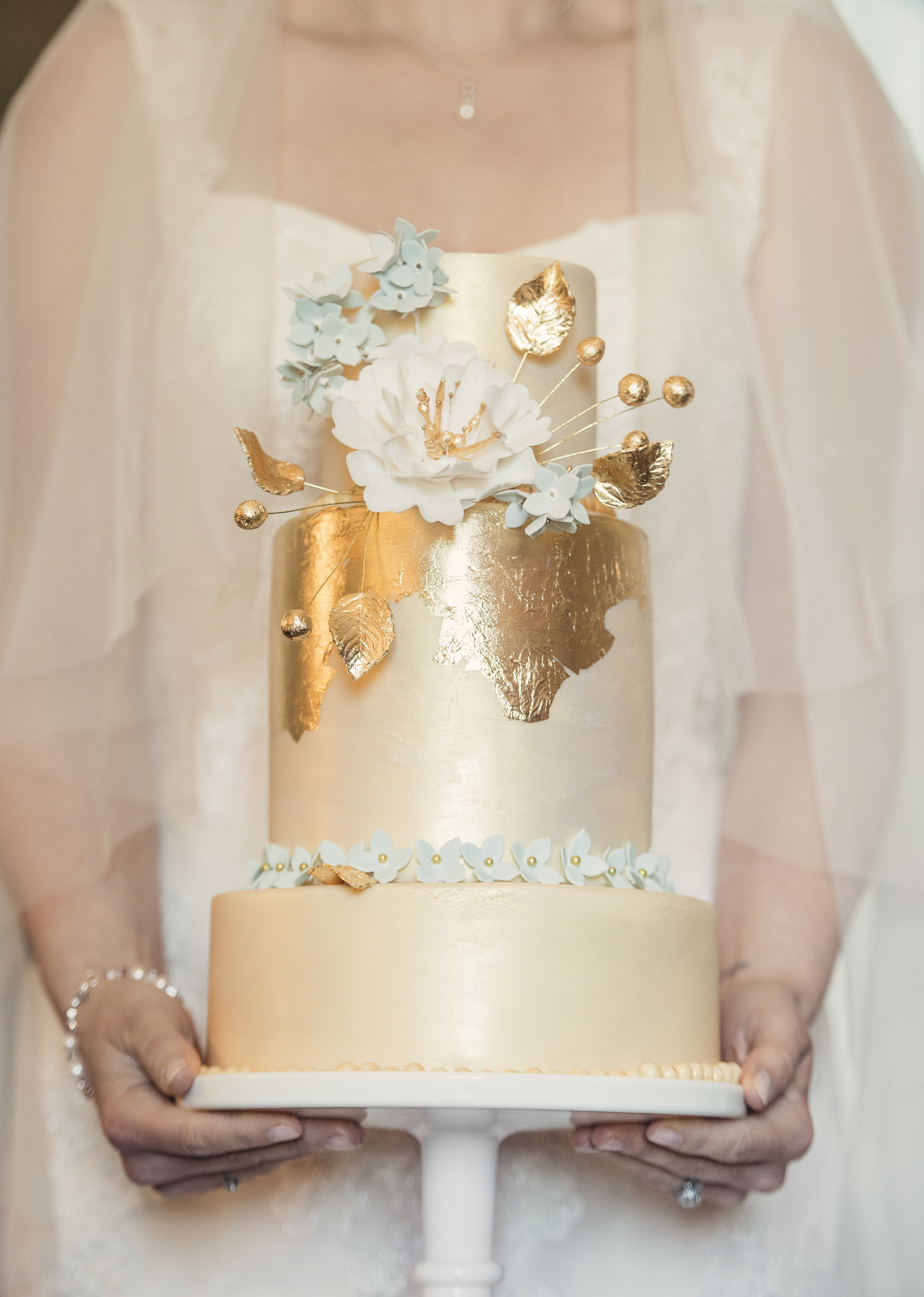 Bride holding 2 tiered gold foiled wedding cake