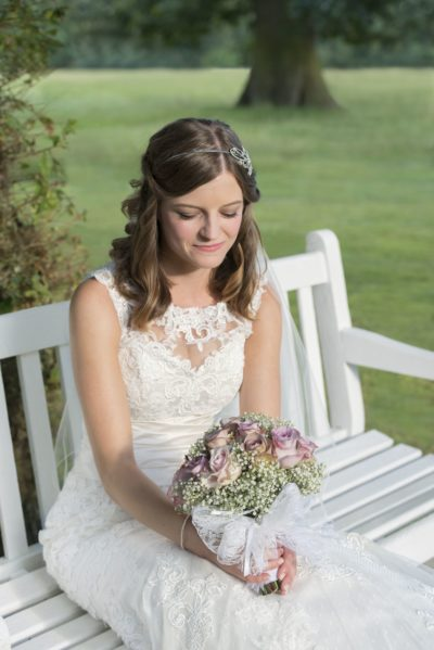 Golden hour award winning shot of a bride sat on a bench and looking into her flowers