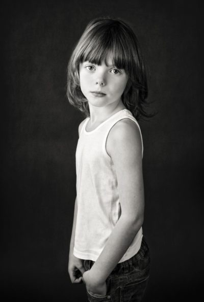 Silver award winning fine art studio photo of boy in vest top and jeans, with long hair