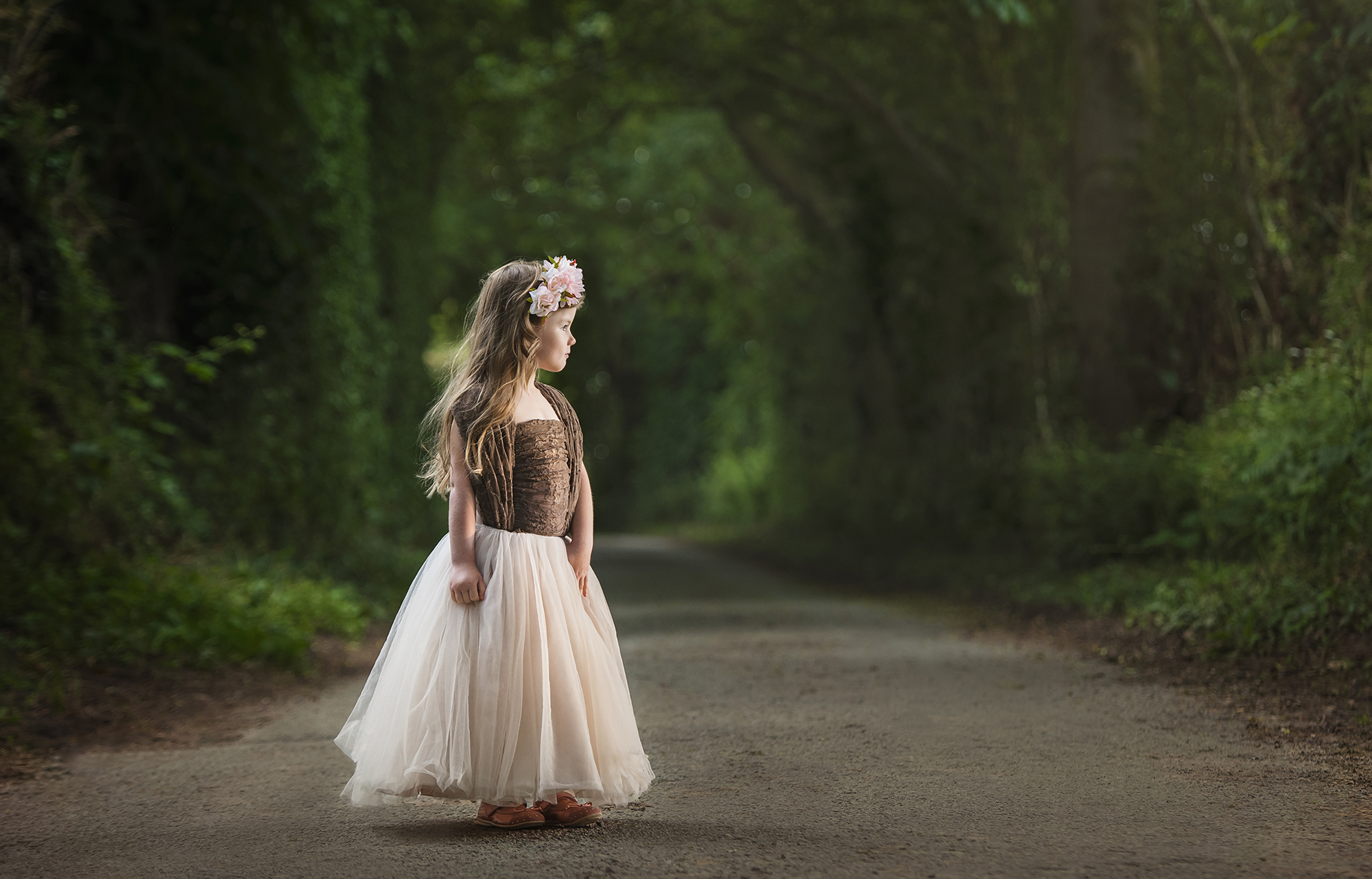 Award winning photo of beautiful little girl on tree lined lane with tulle skirt looking into the golden hour light with a floral crown. Little fine art princess