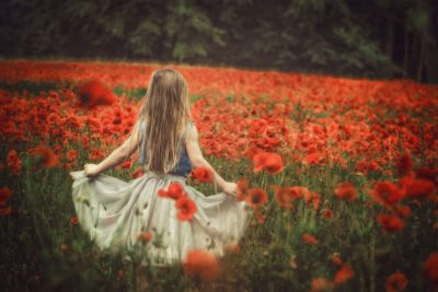 Beautiful fine art photo of girl inred poppy field with flowing skirt