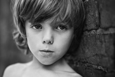 Silver award winning photo in black and white of boy leaning against an old brick wall and looking into camera