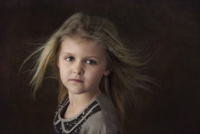 Fine art head shot of little blond 5 year old girl with hair blowing