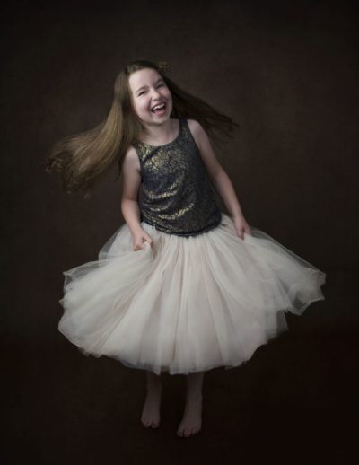 Fine art studio photo of 8 year old girl dancing and laughing in tulle skirt and hair flowing