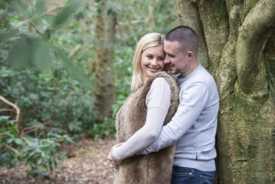 Couple pose for their pre-wedding shoot by a tree in a woodland