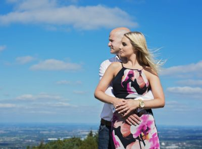 Husband and wife to be pose in the clouds at the top of the Wrekin in Telford