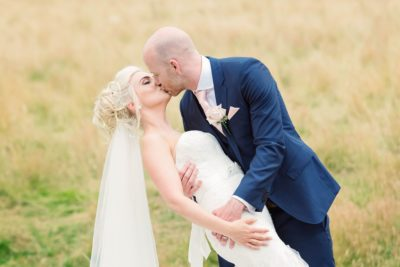 Groom goes in for a romantic dip kiss with the bride at Brockencote Hall Wedding Venue