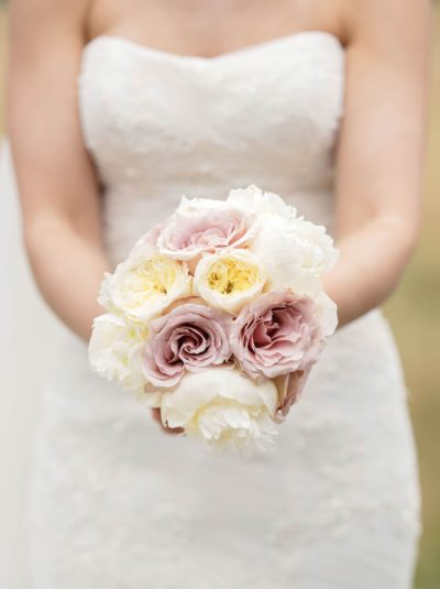 Bride holds beautiful bouquet of peonies and roses