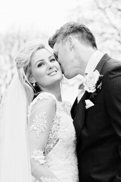 Romantic black and white photo of groom kissing bride