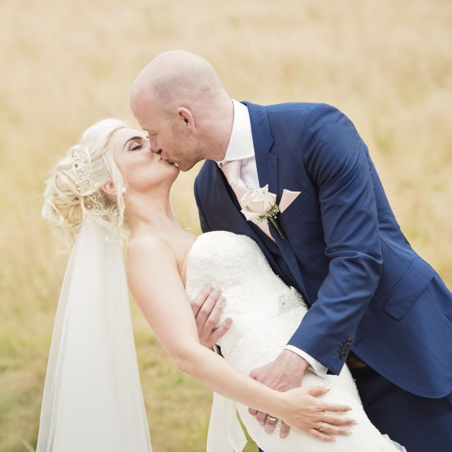 Bride and grrom in fine art wedding photo, groom tilts the bride for a kiss
