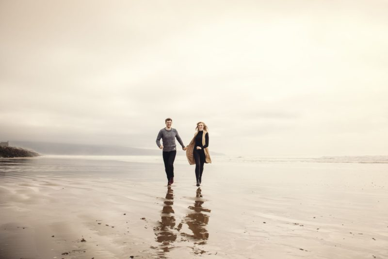Man and wife to be run along the beach together during pre-wedding shoot